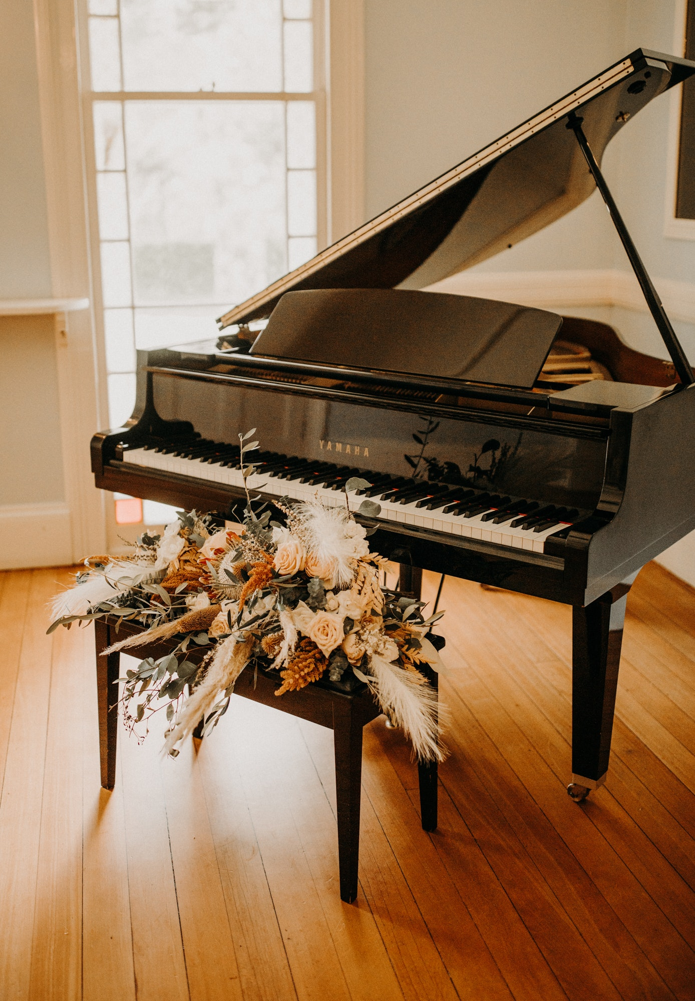Grand piano with bouquet on stool