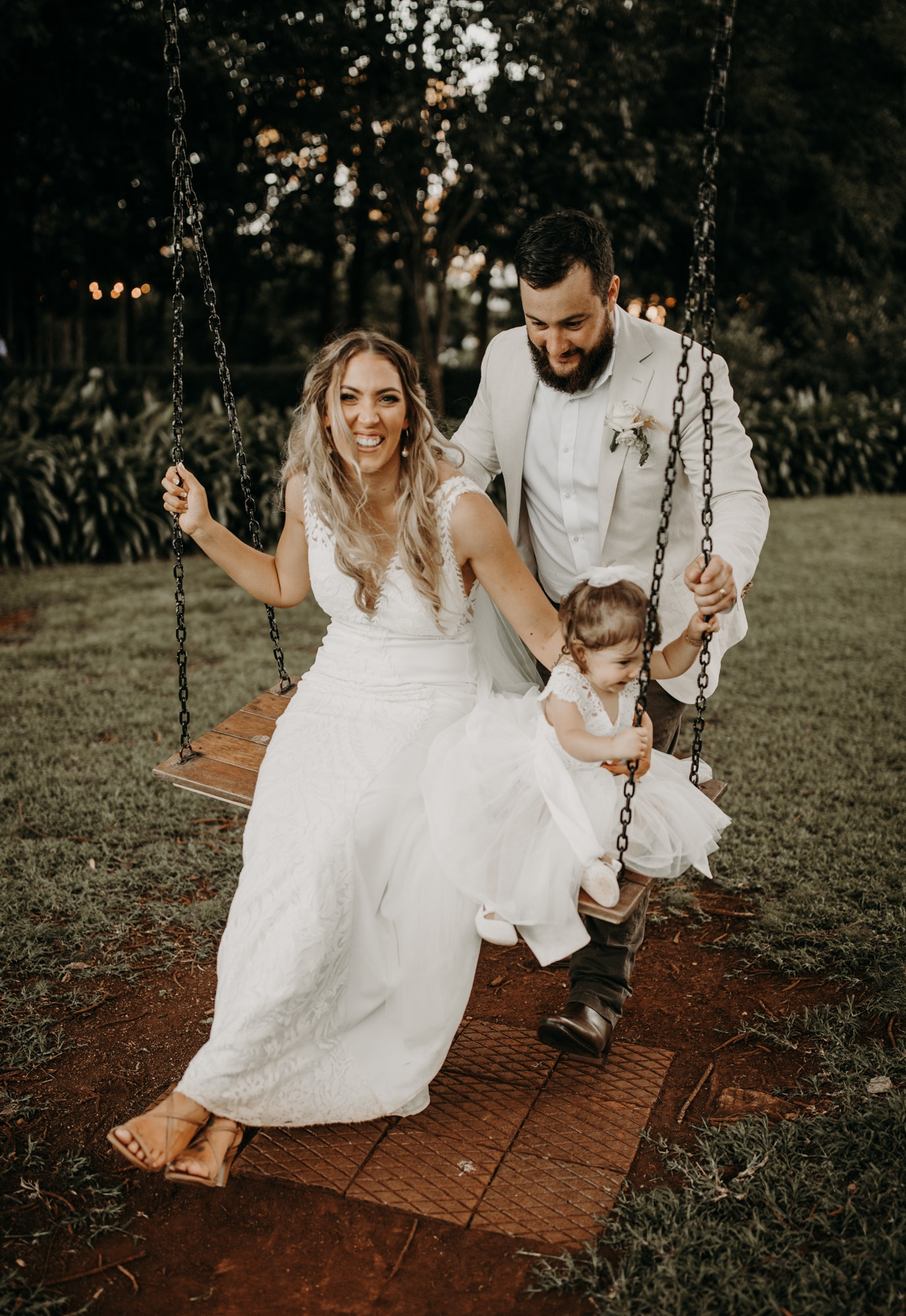 Bride and groom on swing with daughter
