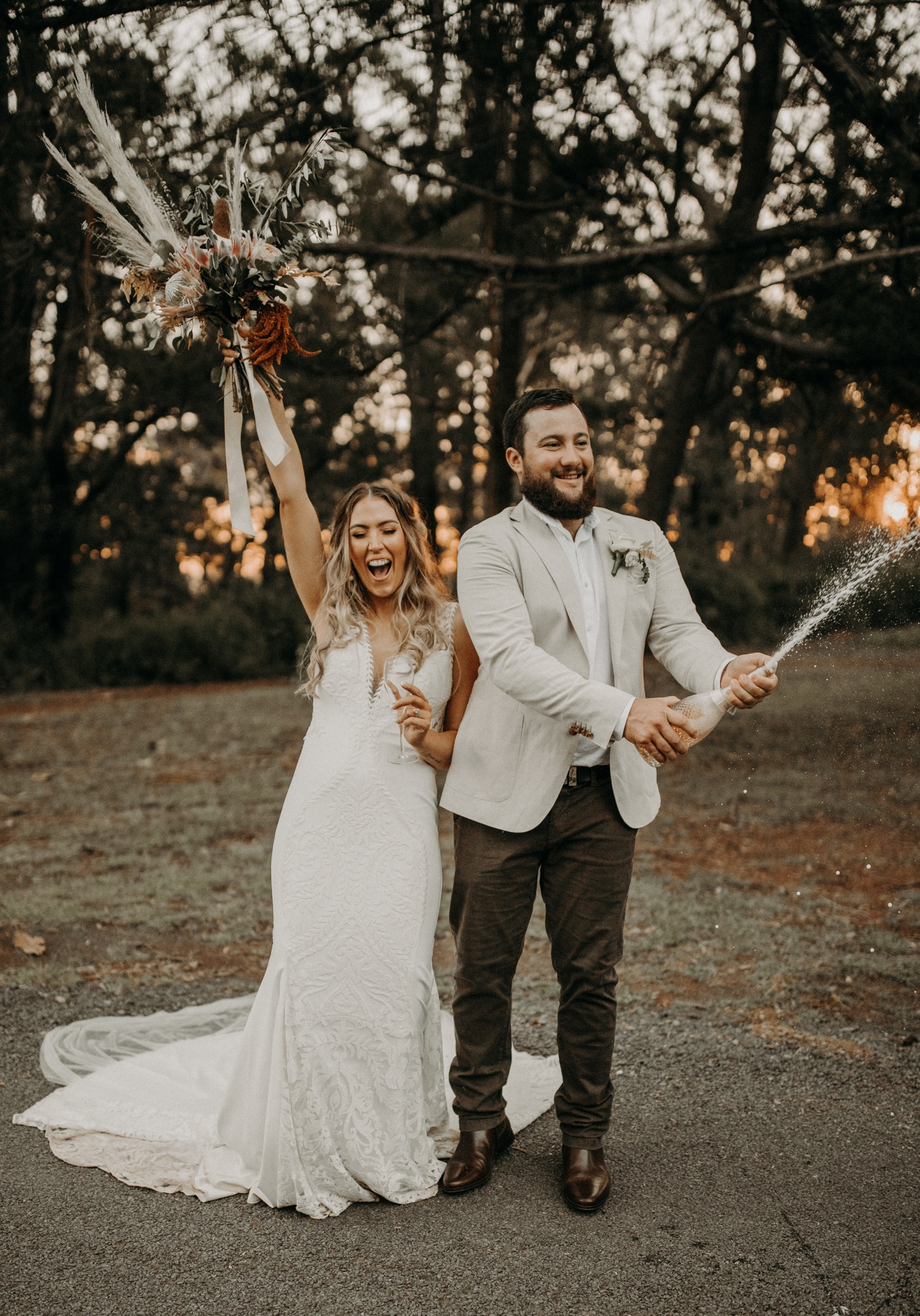 Bride and groom popping a bottle of champagne