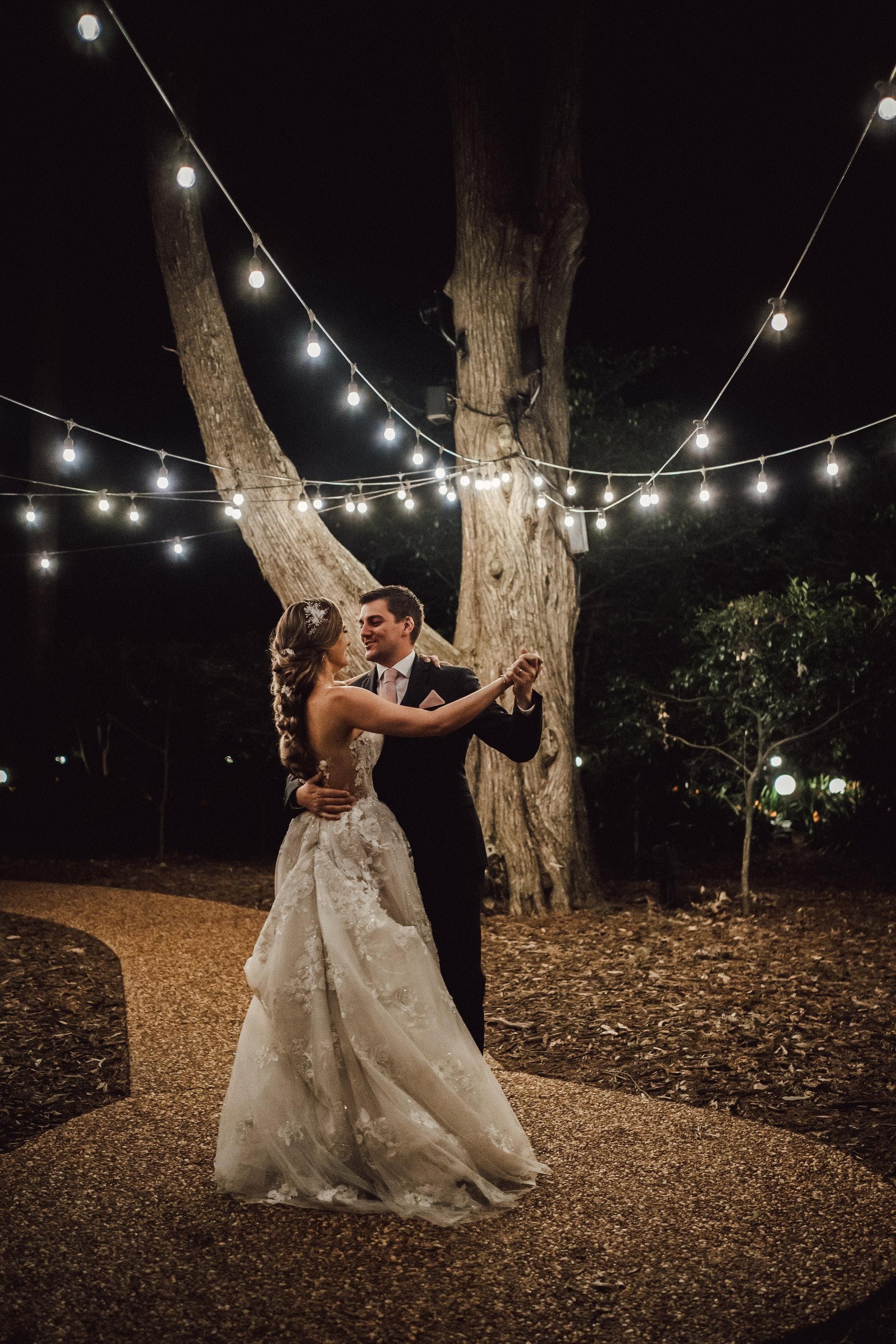 Bride and groom dancing under festoon lights