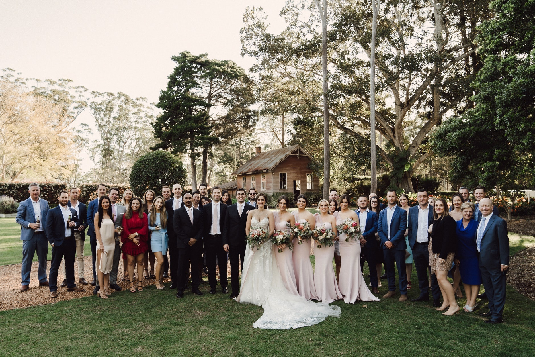 Group shot in gardens of all wedding guests