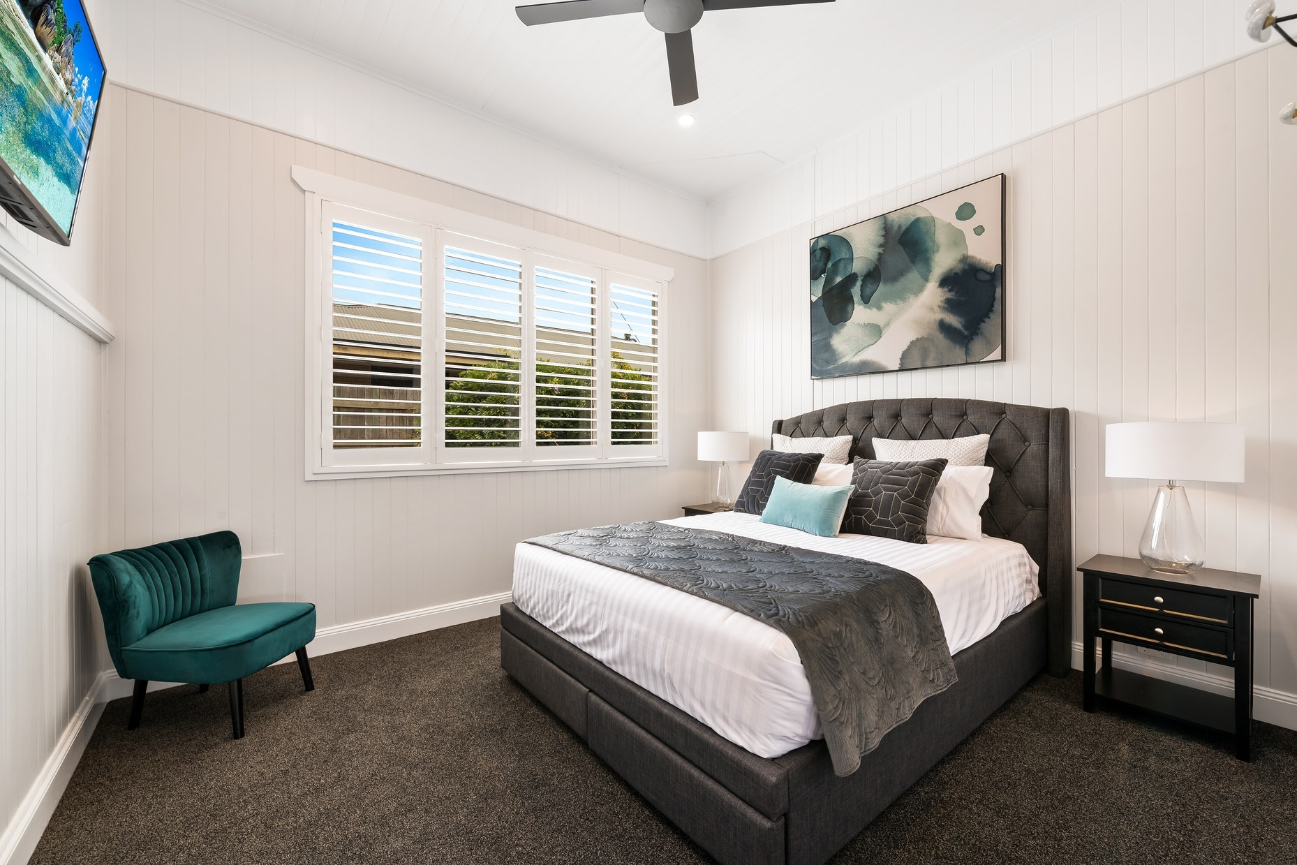 Bedroom with large artwork above bed and chair in the corner