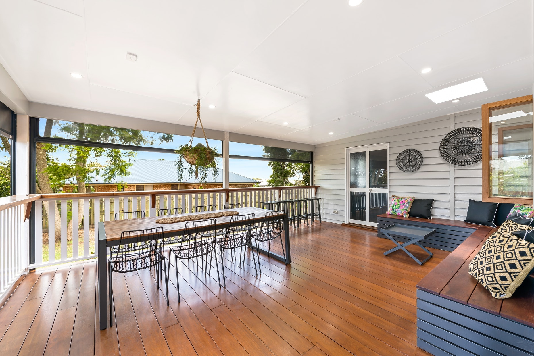 Deck with wooden table, hanging plant and corner bench seating