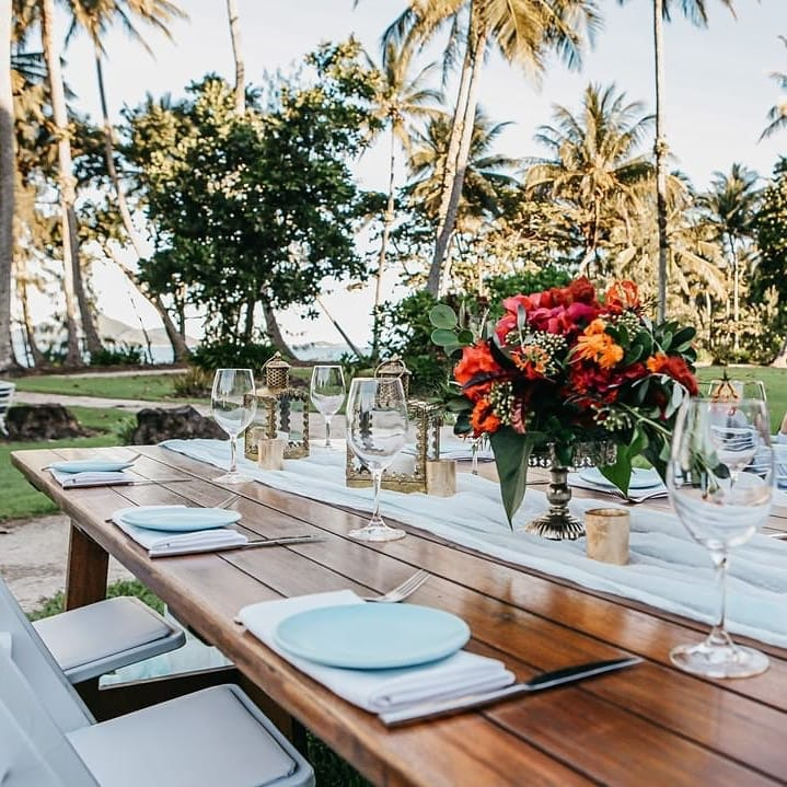 Table set with flowers and cutlery with palm trees in background