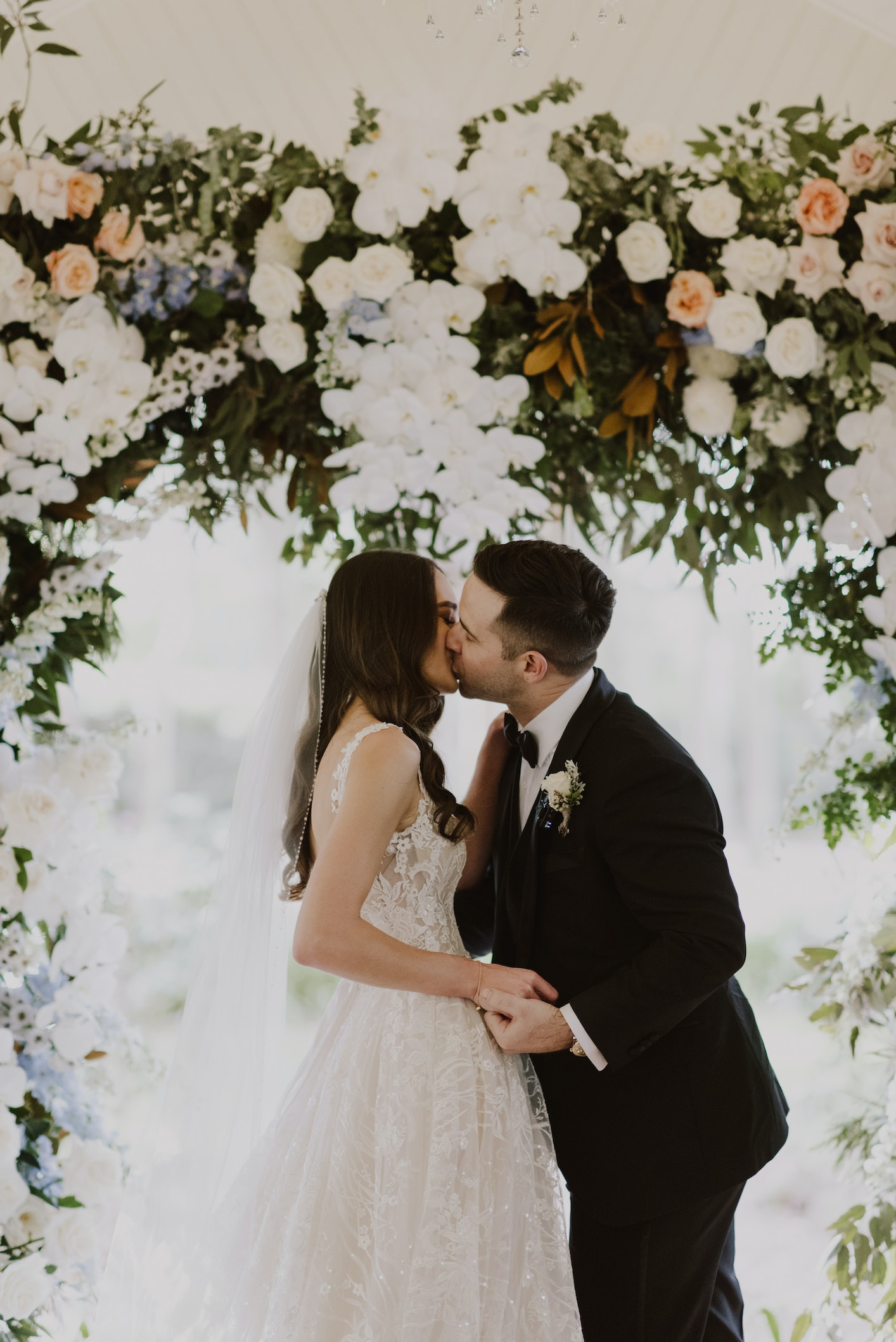 Bride and groom kissing under arbor