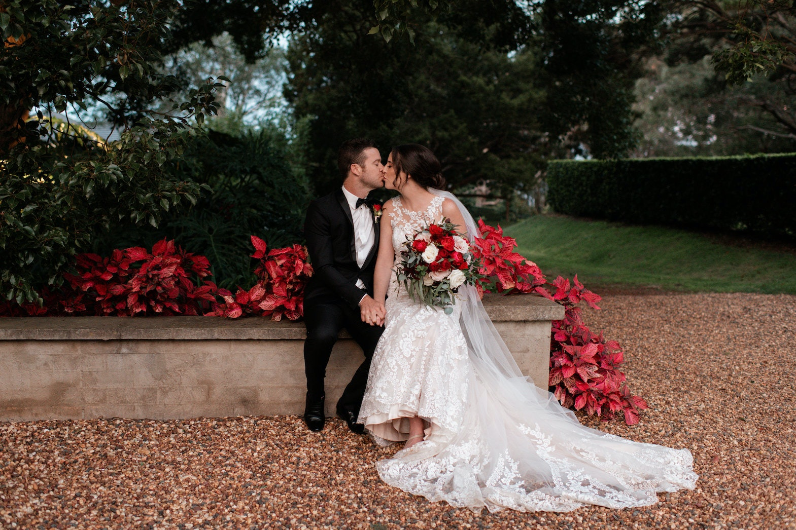 Bride and groom sitting down kissing
