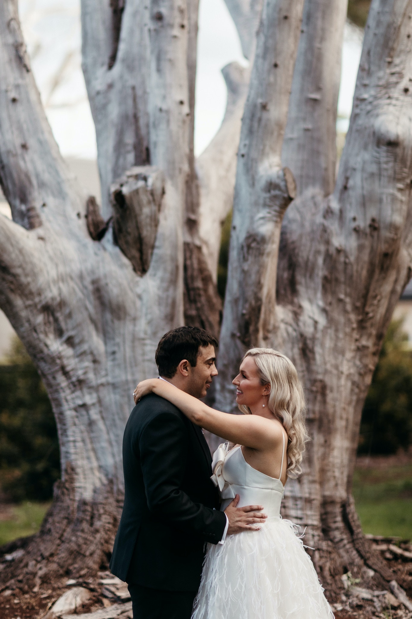 Bride and groom standing in front of tree