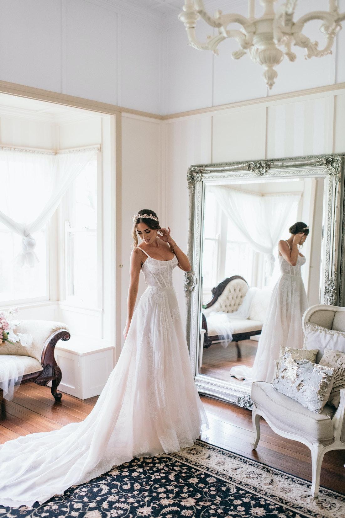 Bride standing in front of mirror in dress