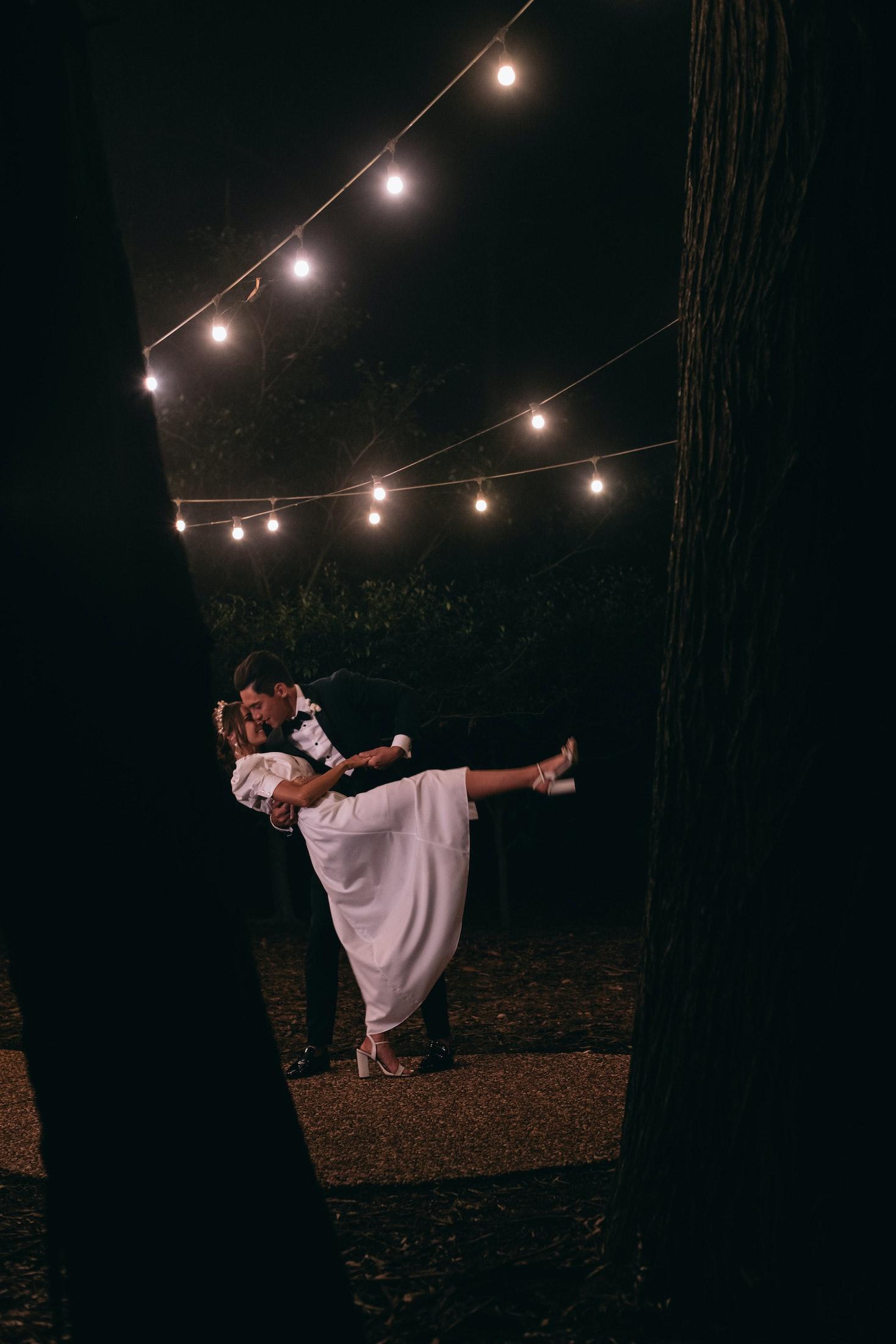Bride and groom dancing oustide