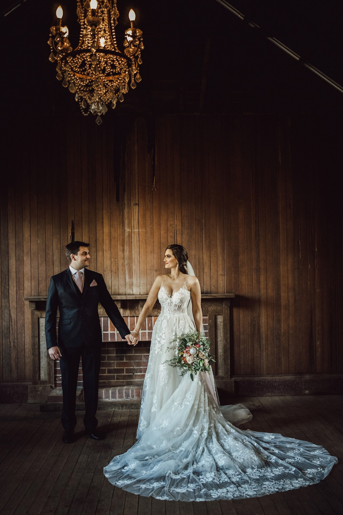 Bride and groom holding hands in old school house