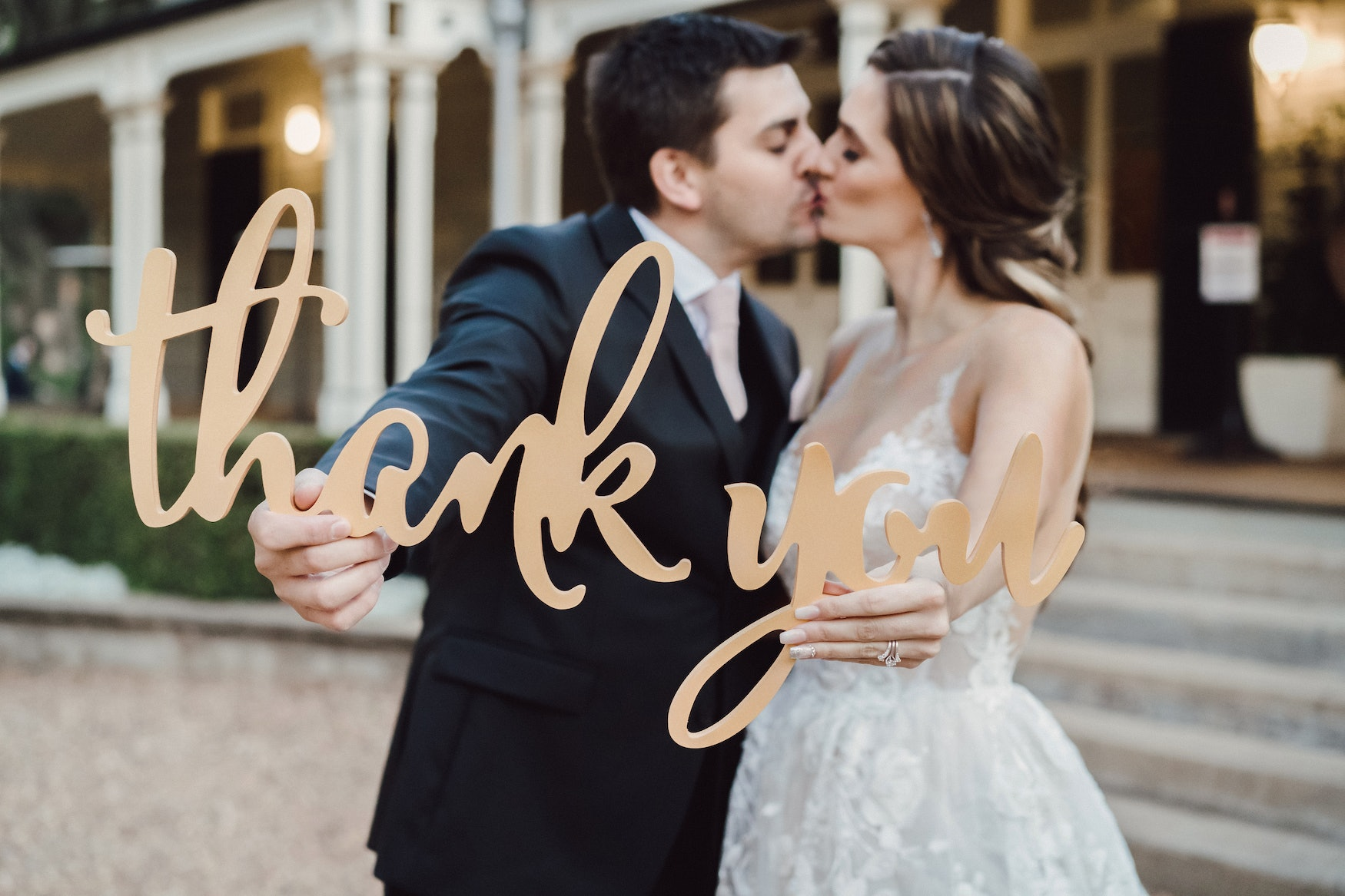 Bride and groom holding 'thankyou' sign