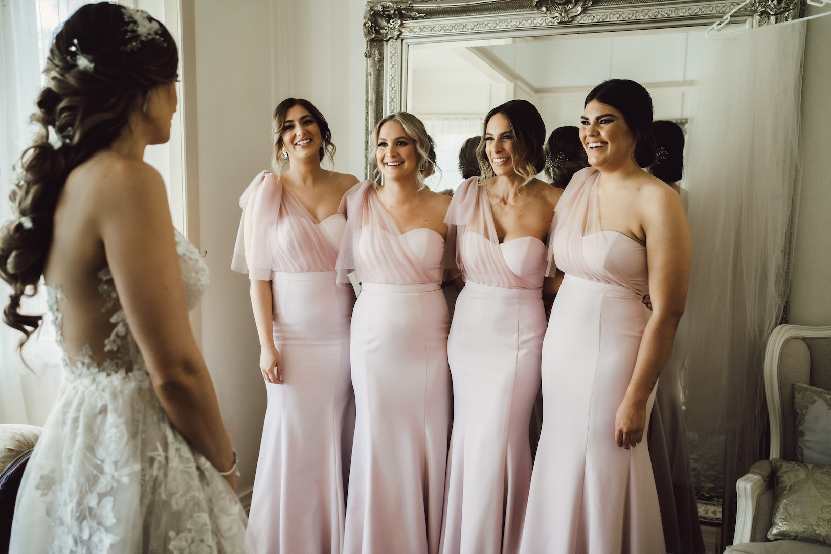 4 Bridesmaids standing in front of bride laughing