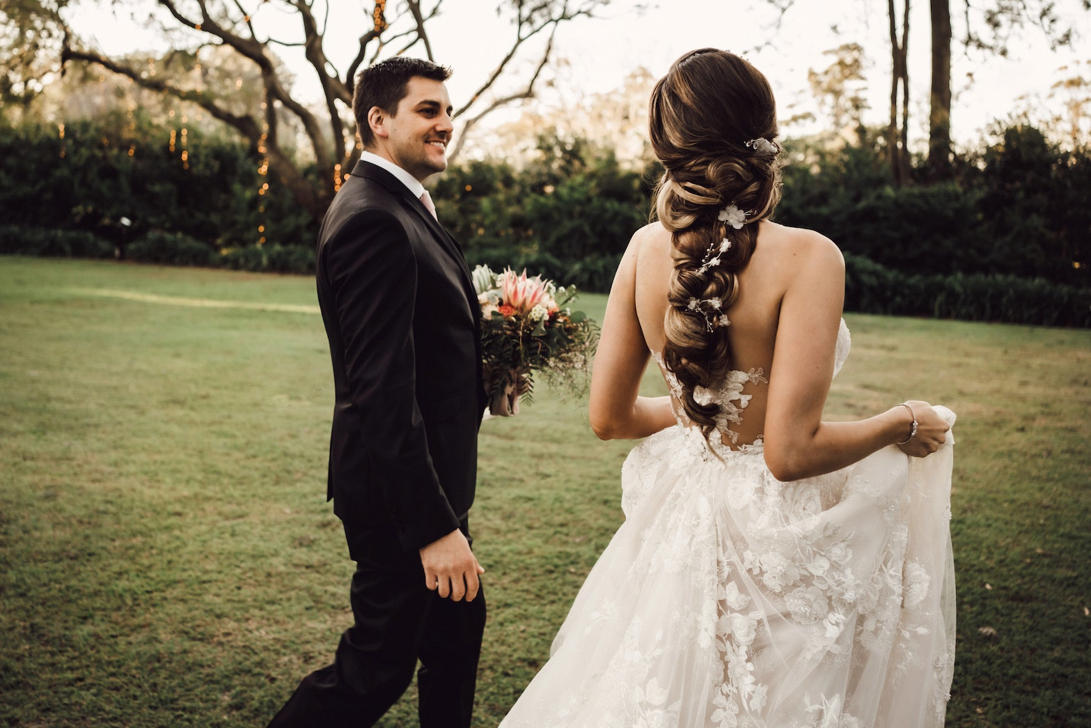 Bride and groom walking through gardens looking at one another