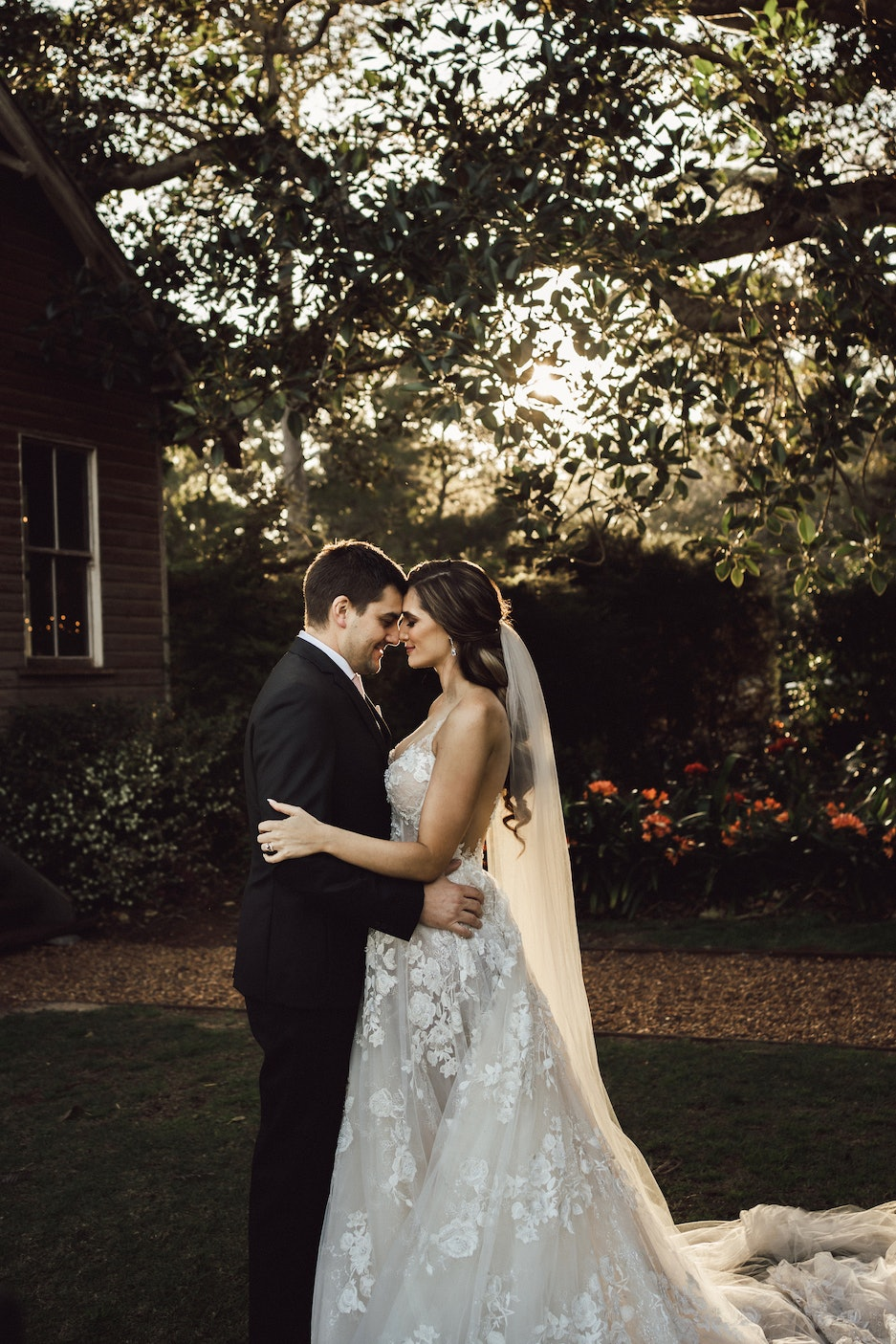 Bride and groom holding one another with their noses touching gently