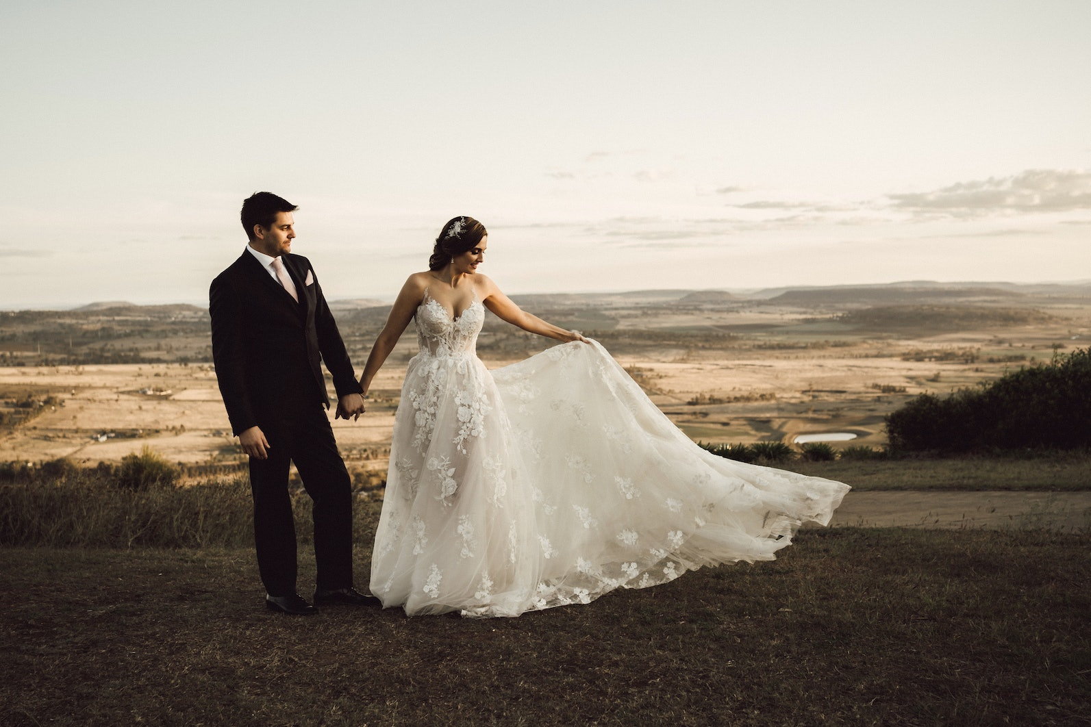 Bride and groom standing on escarpment, bride holding the train of her dress to one side