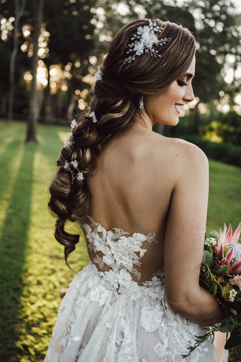 Bride looking down holding a bouquet with long braided hair with flower accessories in it