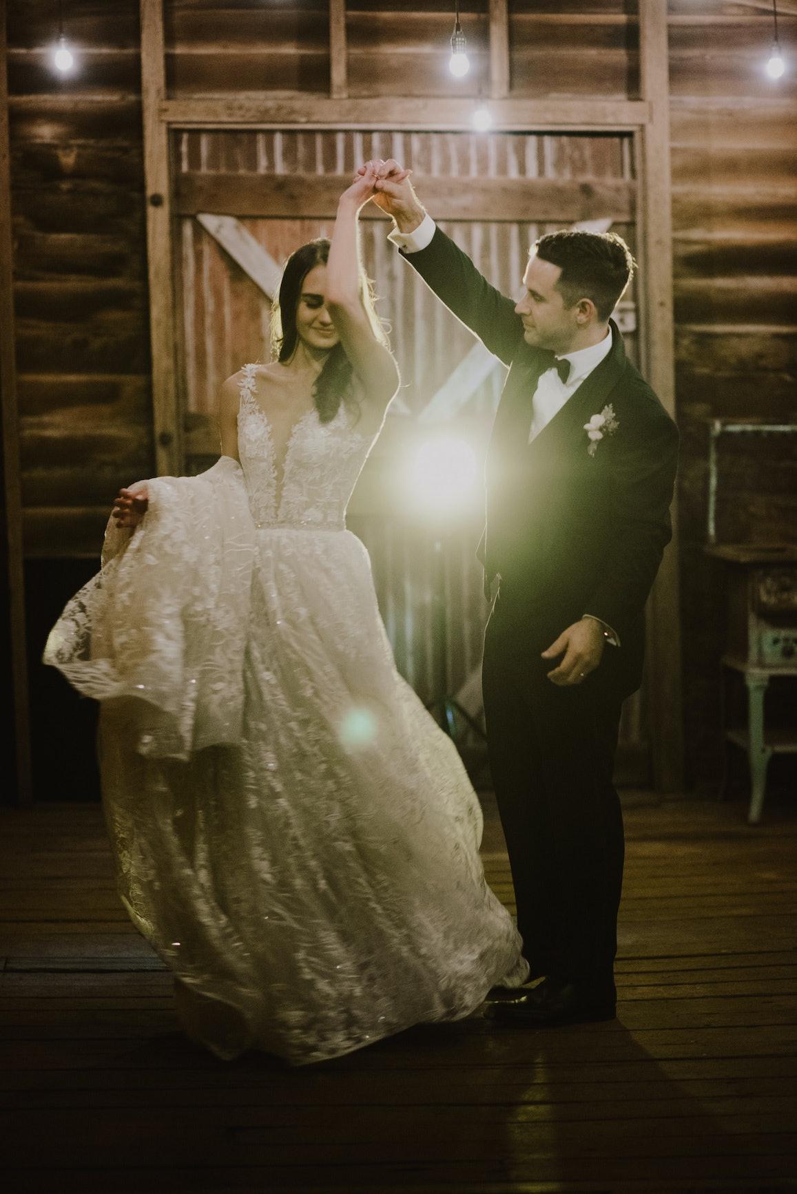 Bride and groom dancing in stables