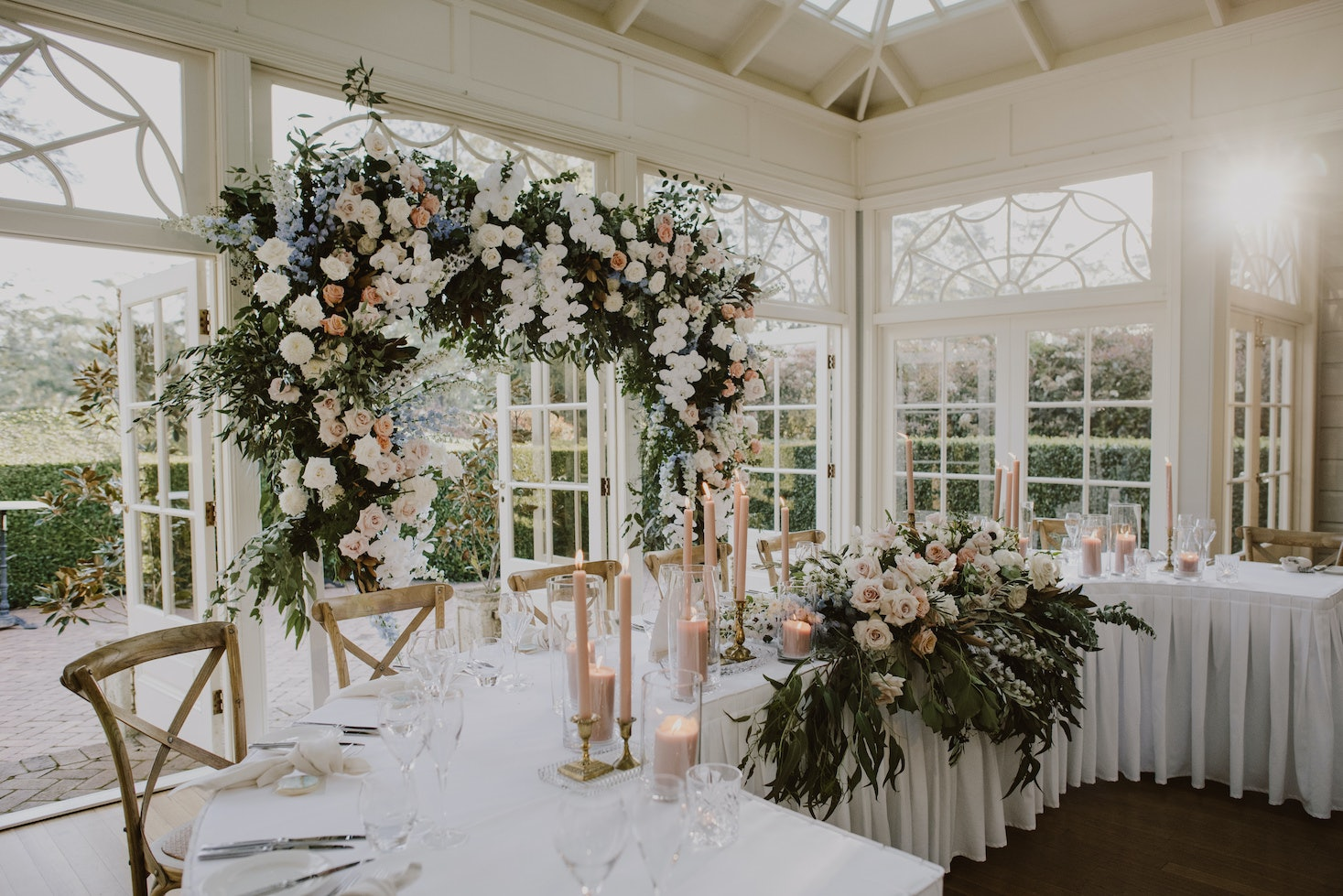 Floral arbour behind wedding parties reception table