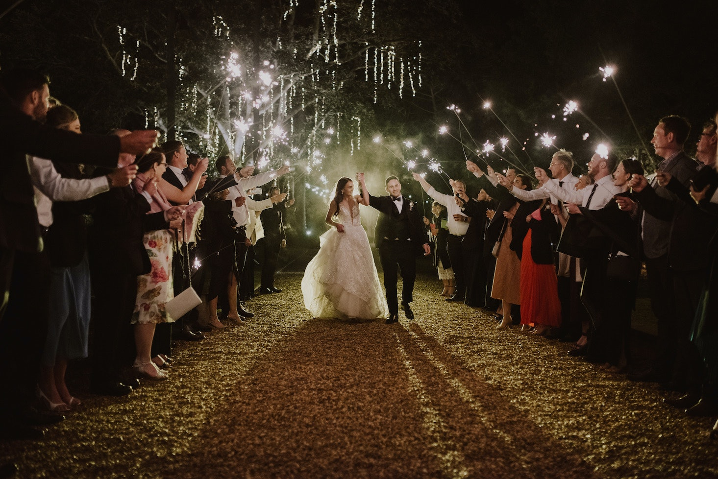 Bride and groom walking down driveway past guests holding sparklers