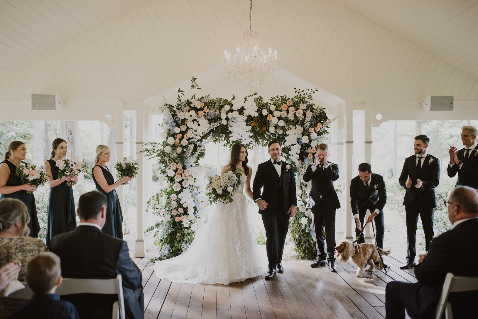 Bride and groom in front of floral arbour