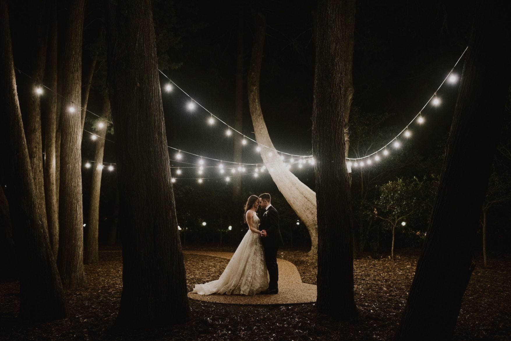 Bride and groom standing under festoon lights at night