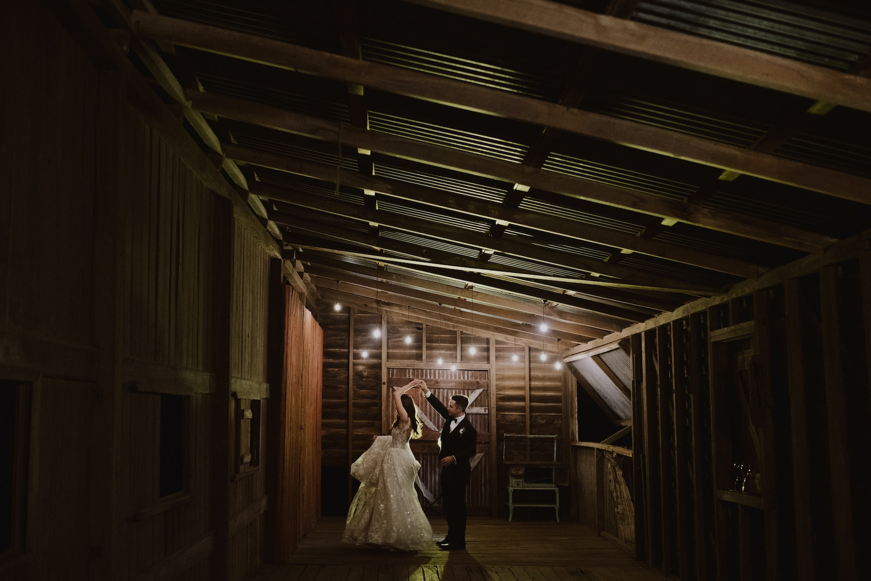 Bride and groom dancing in stables together
