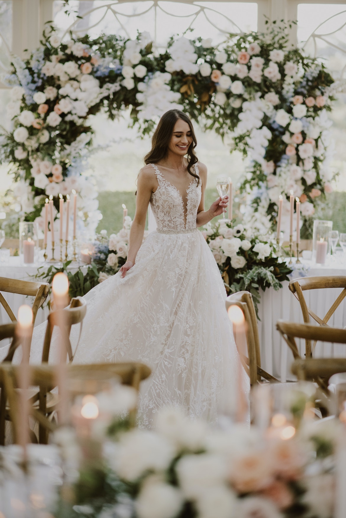 Bride holding a glass of champagne standing in front of a floral arbour