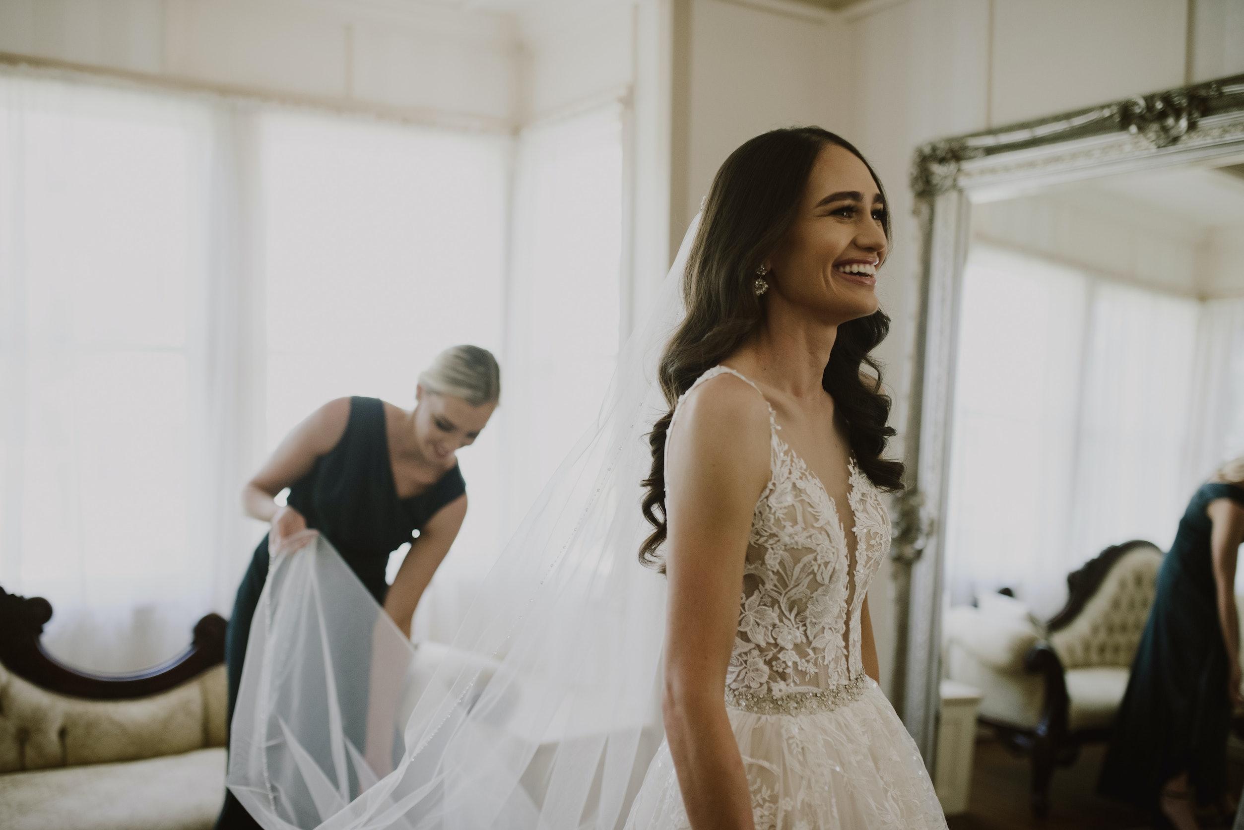 Bride laughing and bridesmaid holding brides veil