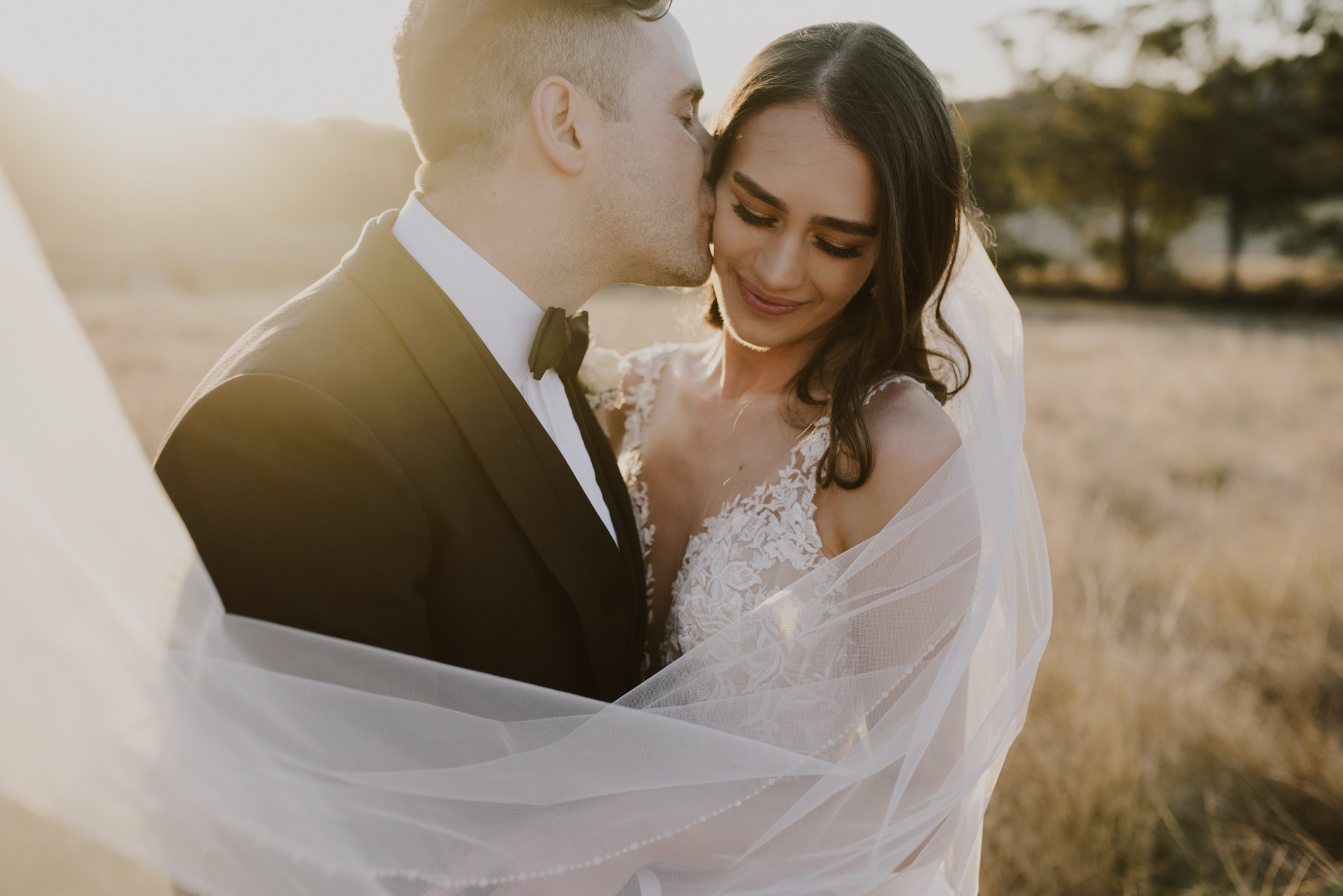 Groom kissing bride with veil blowing in the wind