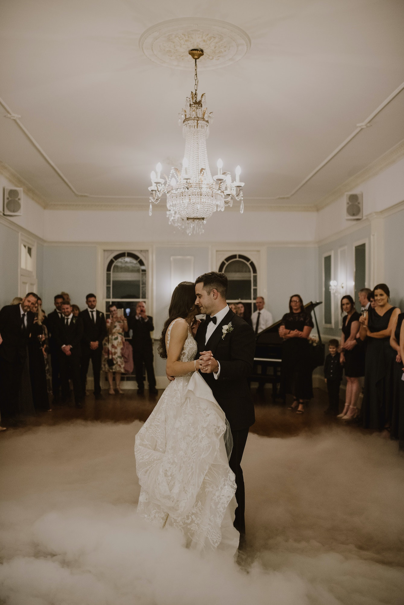 Bride and groom dancing in ballroom with smoke machine