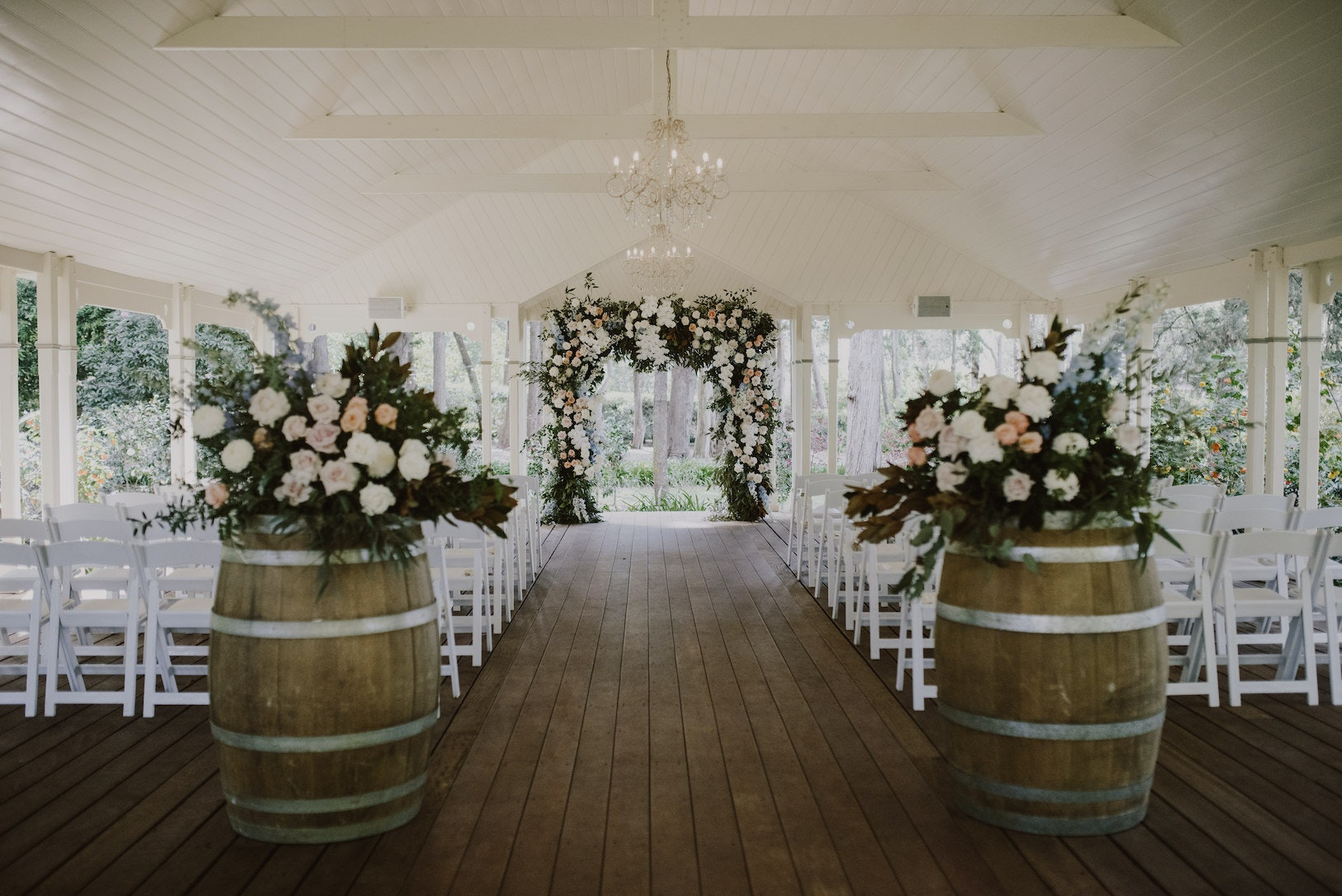 Wine barrels with floral arrangements on top and floral arbour in the middle