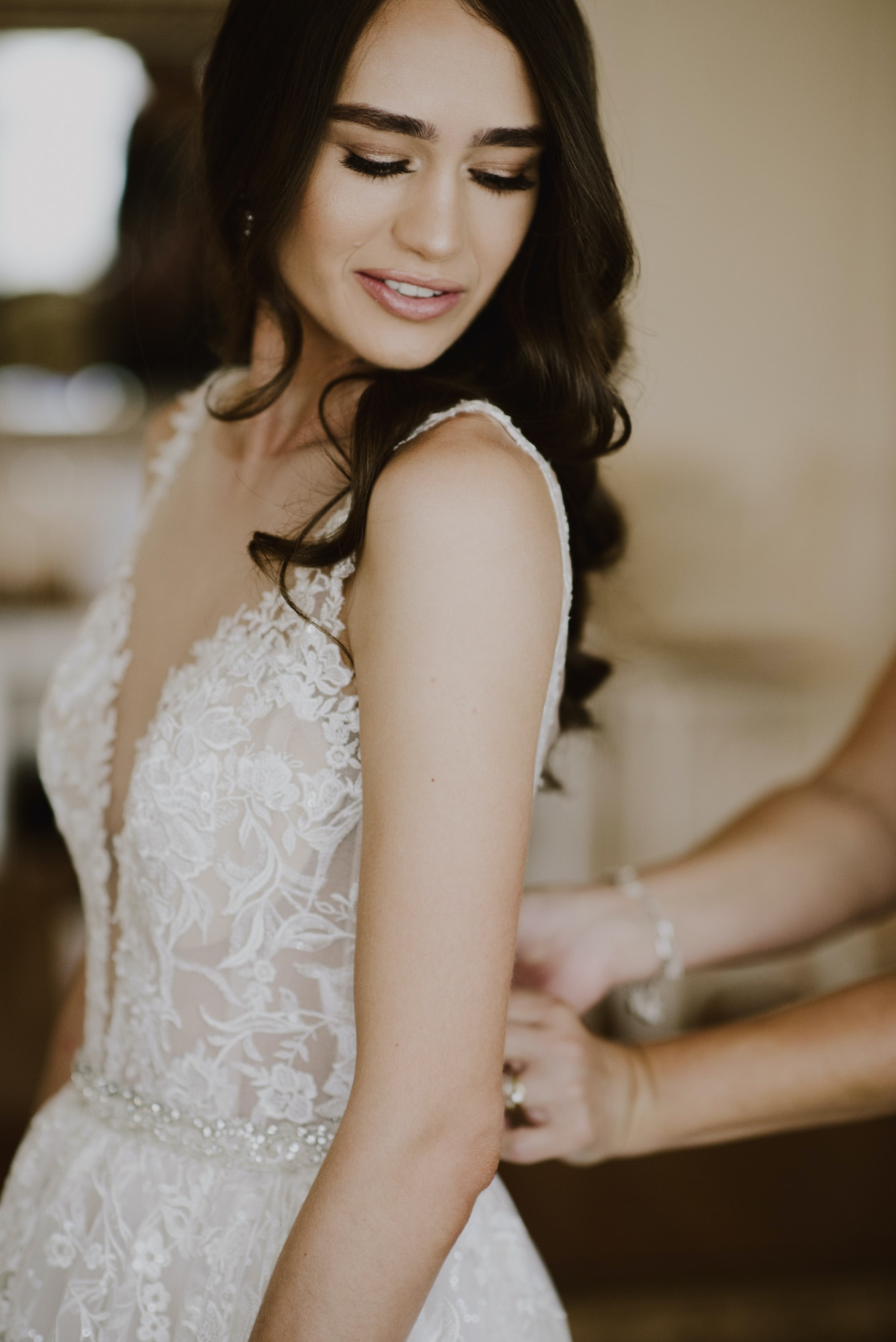 Bride looking over her shoulder at the back of her dress