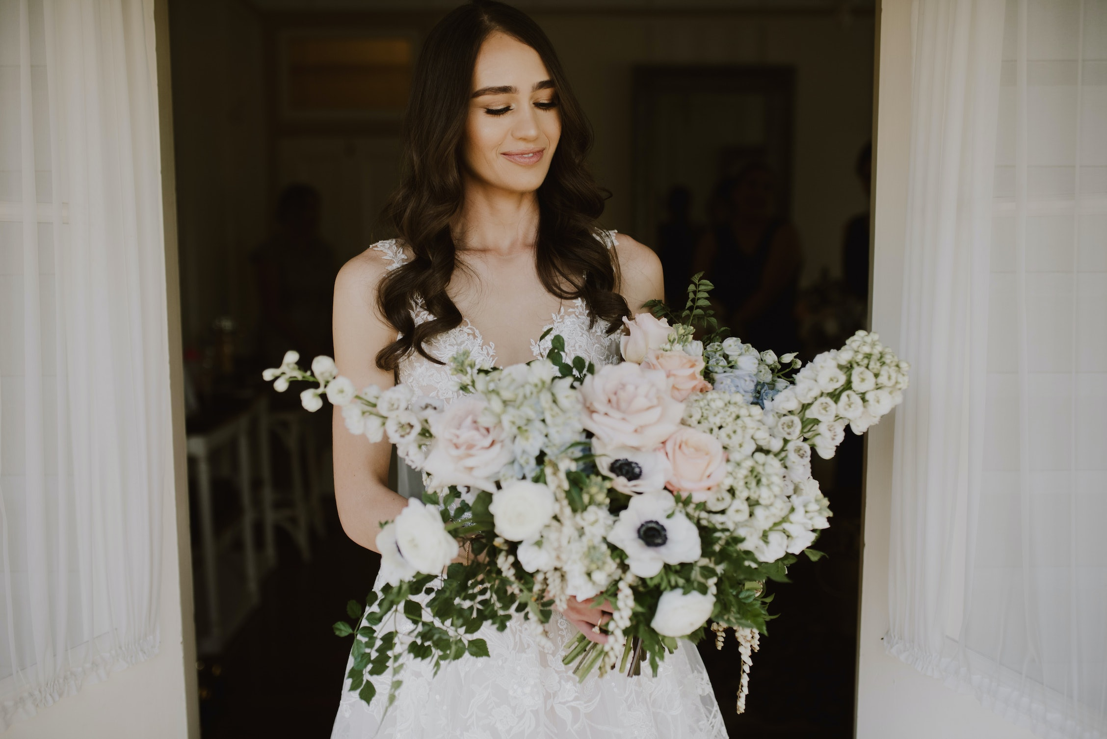 Bride holding a large bouquet with pastel coloured flowers