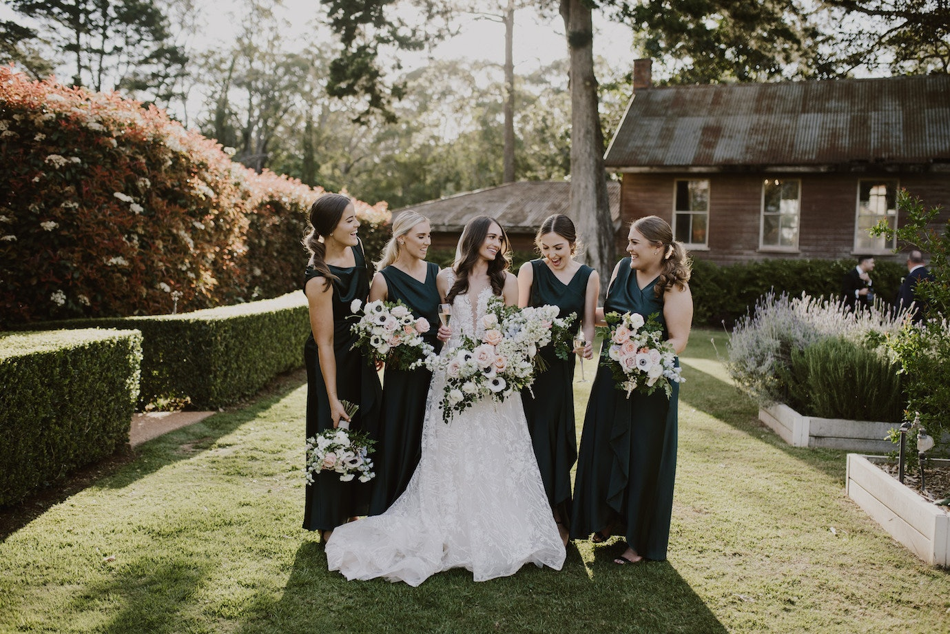 Bride standing between her bridesmaids all holding bouquets