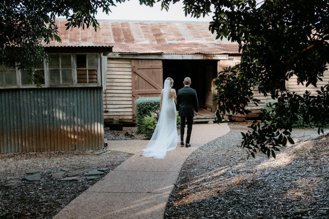 Bride and groom walking towards stables