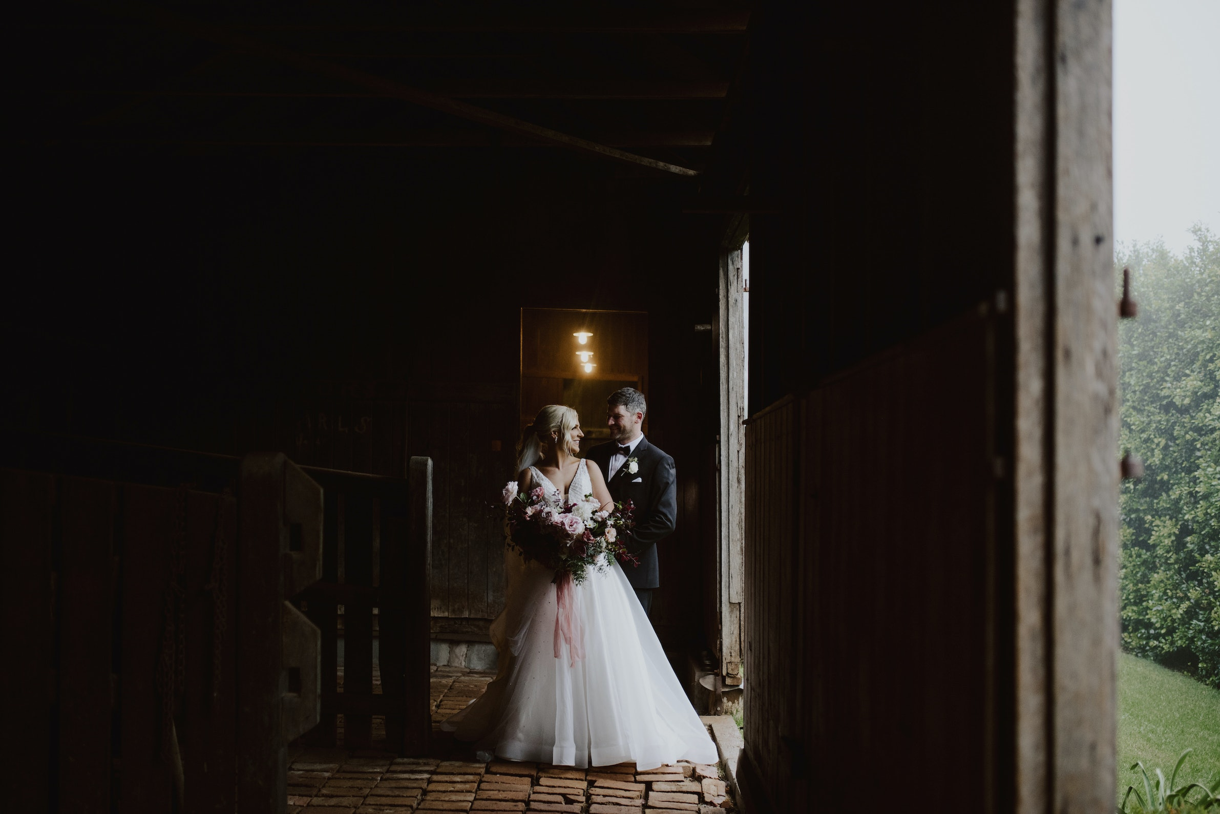 Bride and groom posing together in stables