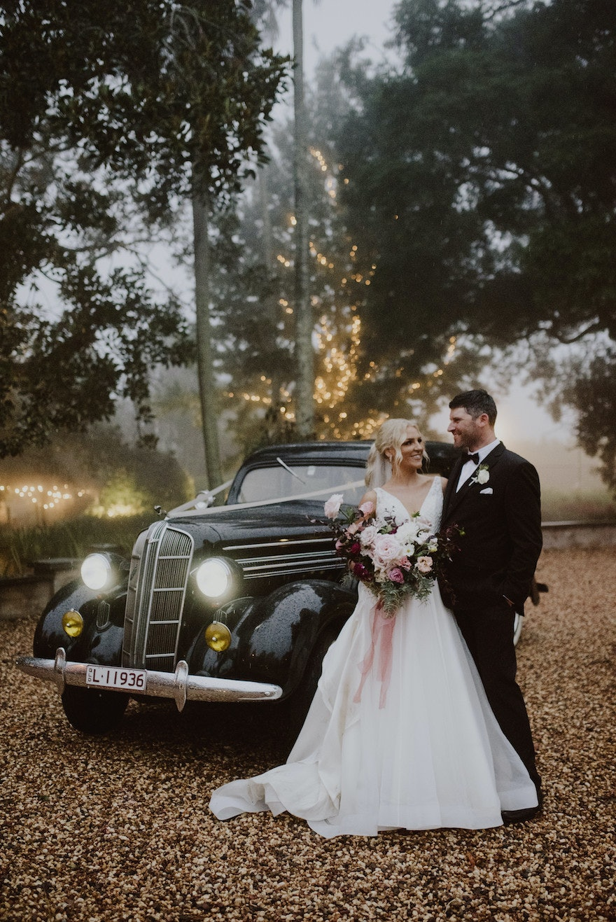 Bride and groom in front of car