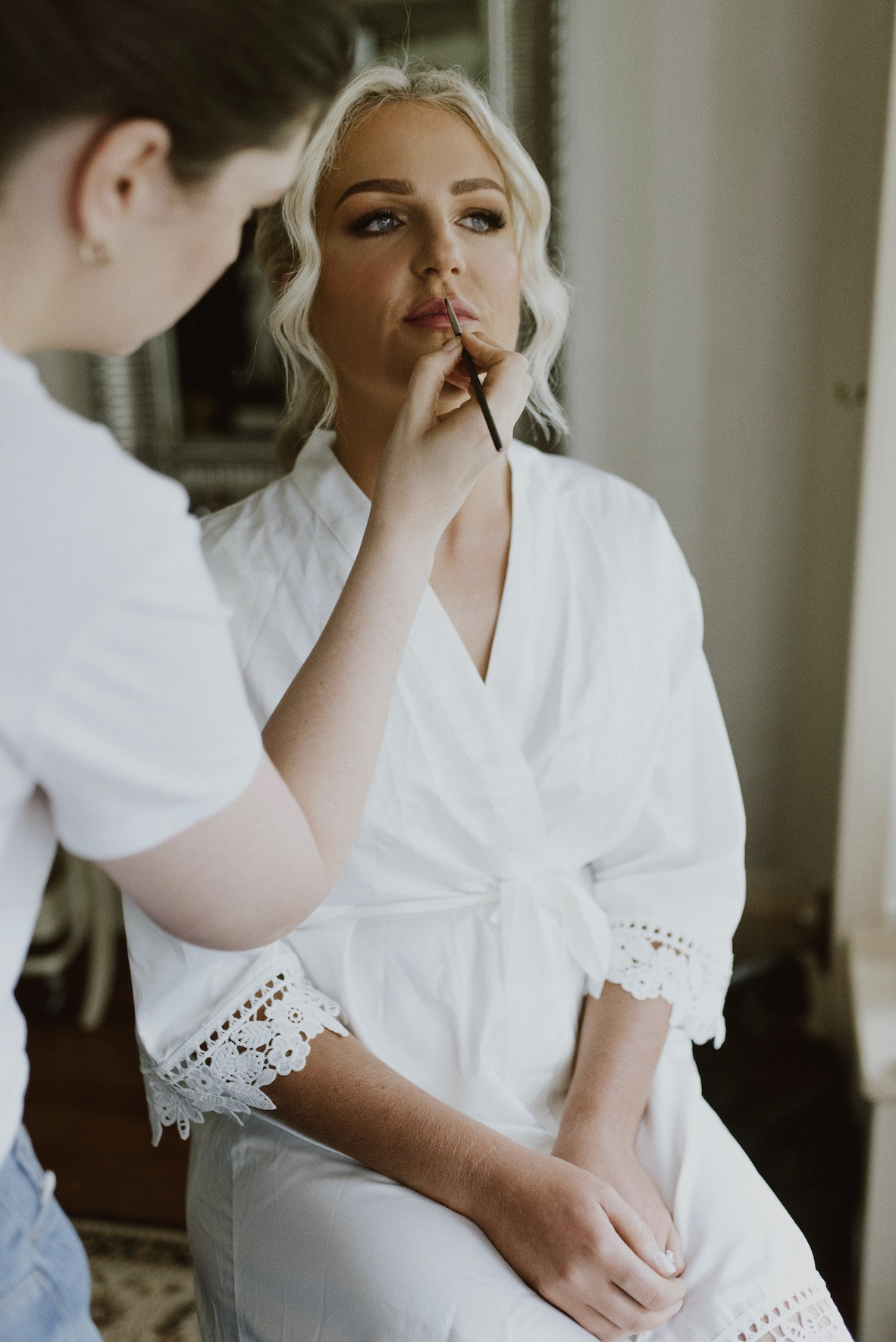 Bride getting makeup applied to her lips