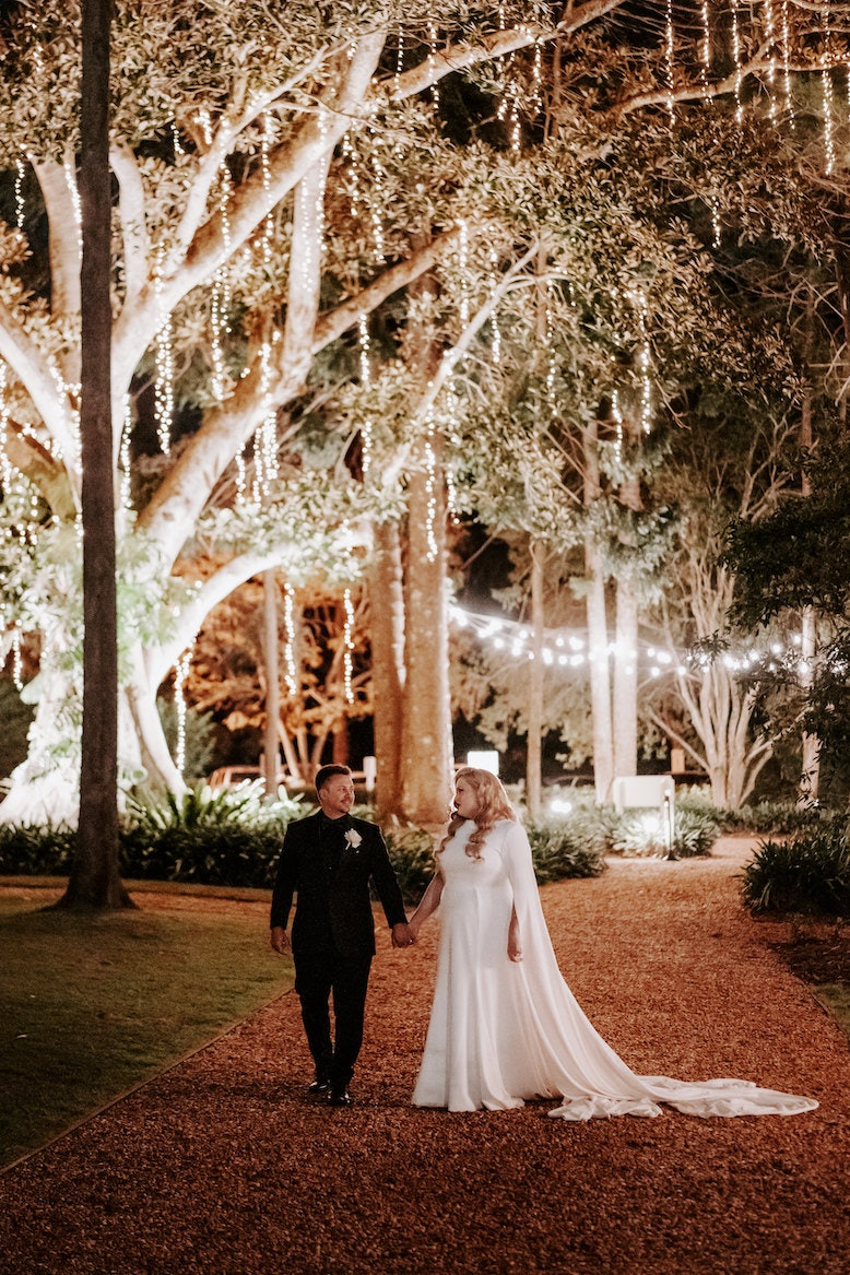 Bride and groom standing under tree lights