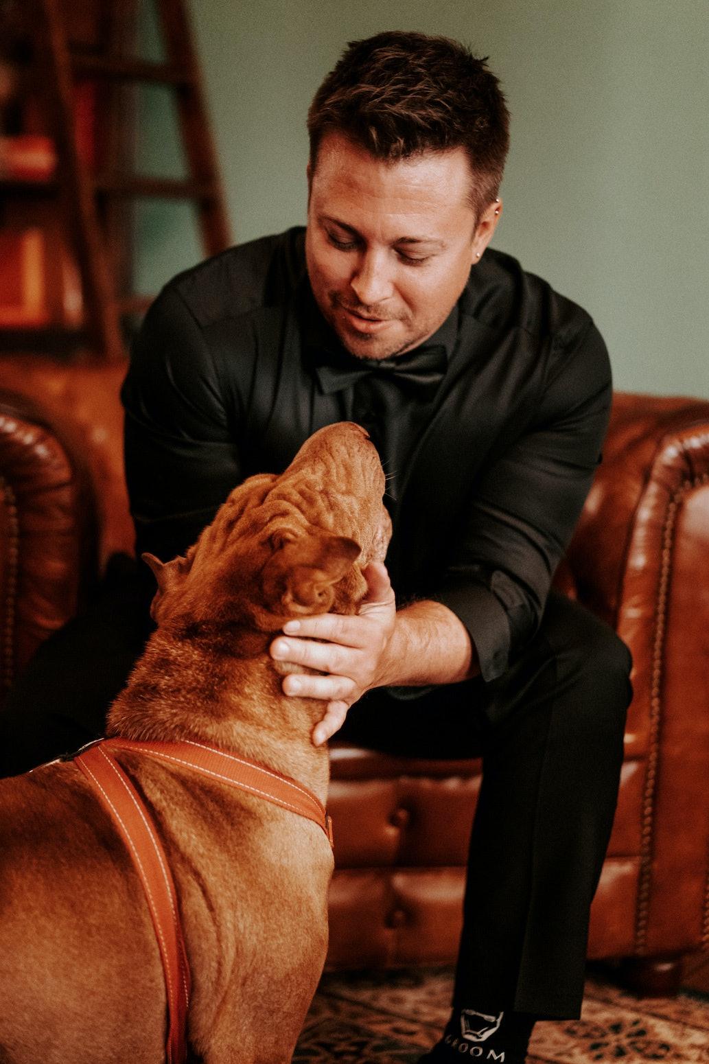 Groom petting dog