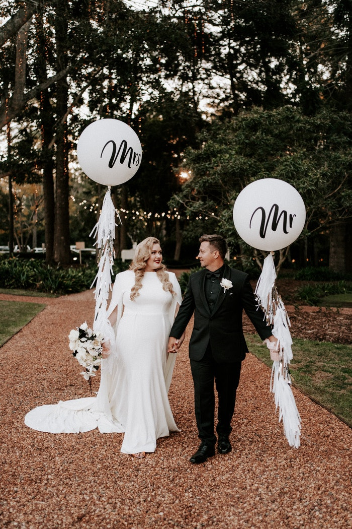 Bride and groom holding balloons