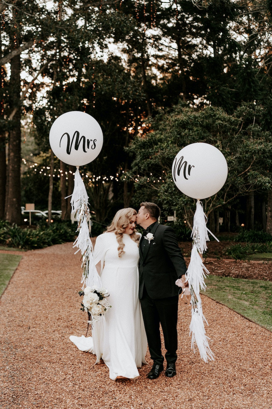 Bride and groom standing on driveway holding balloons