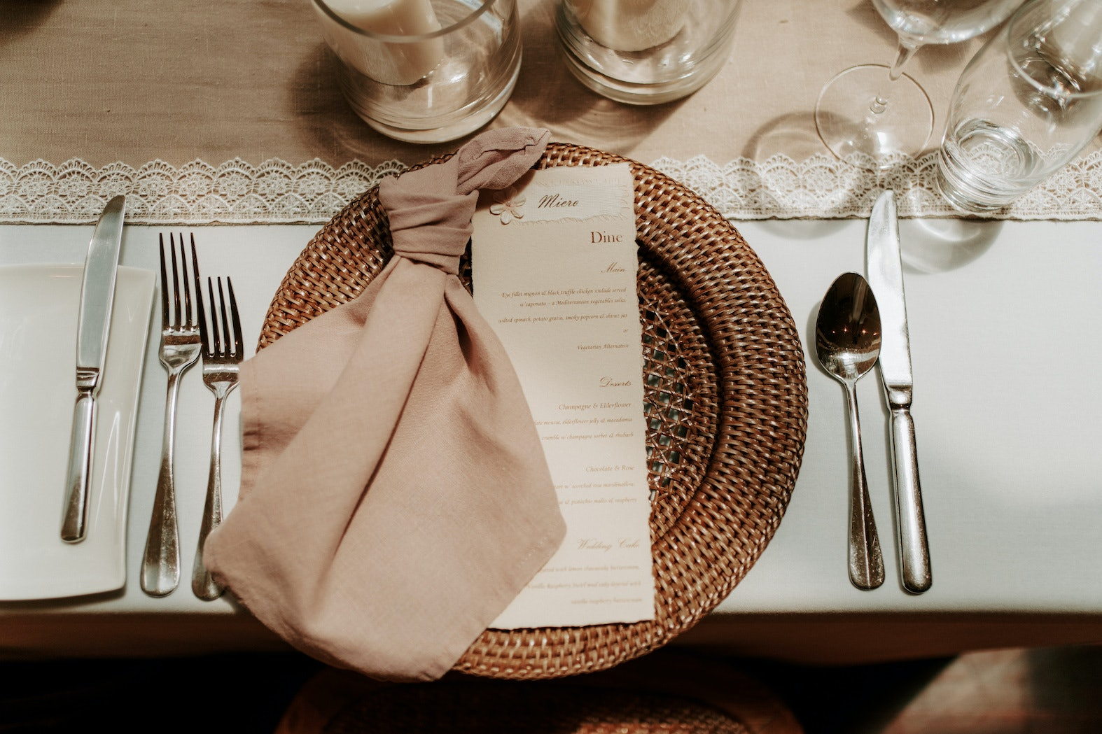Tables setting with rattan plates, linen and namecards