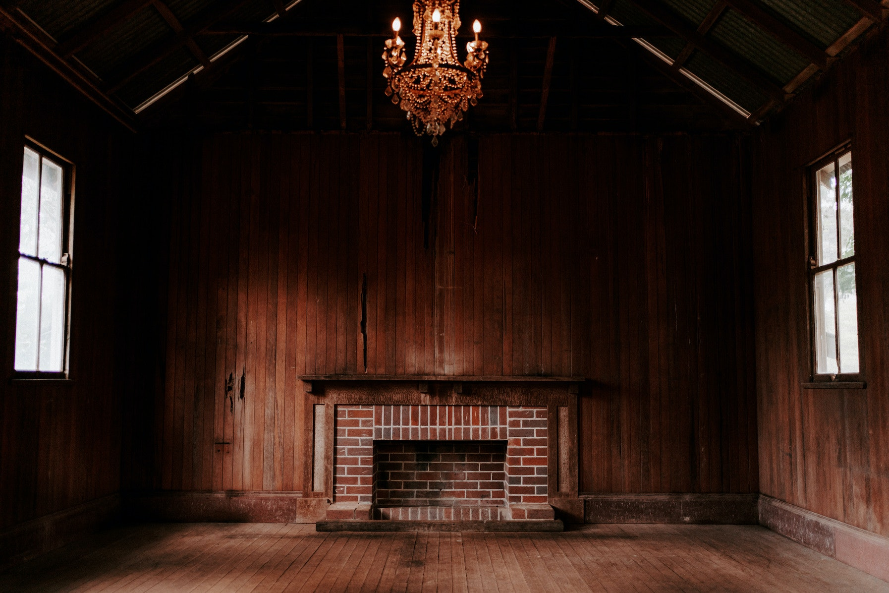 Old brick fireplace with chandelier hanging above