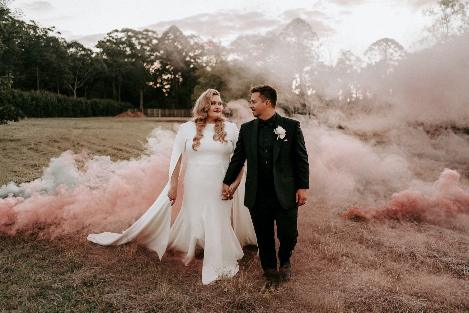 Bride and groom walking along with smoke in the background