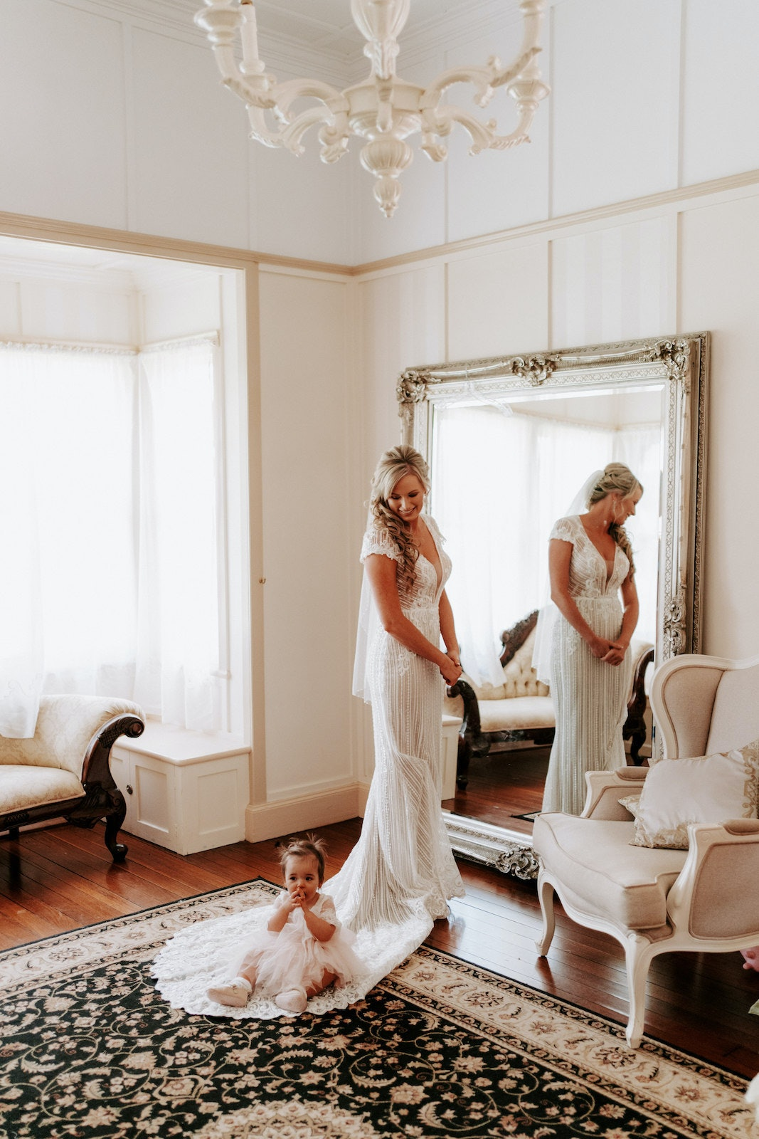 Bride standing in front of mirror with flowergirl
