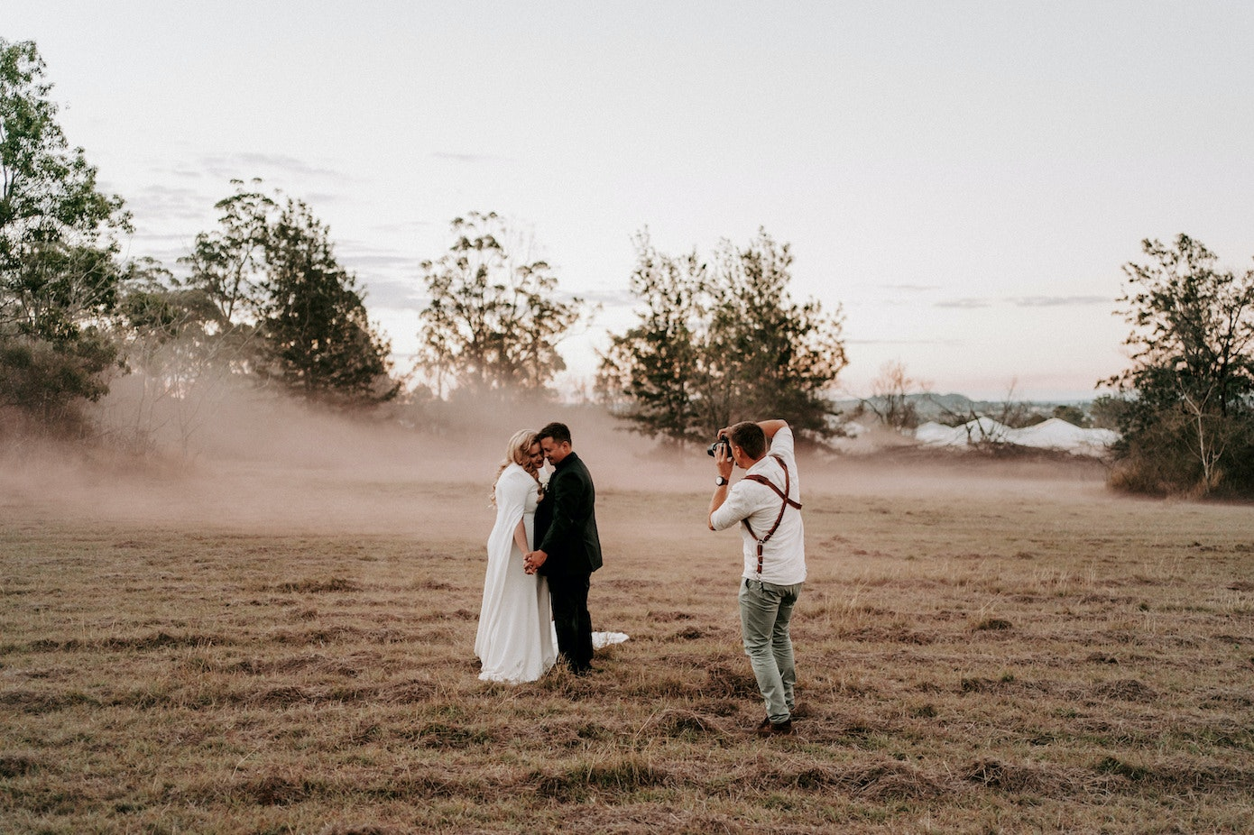 Bride and groom standing in a field with photographer