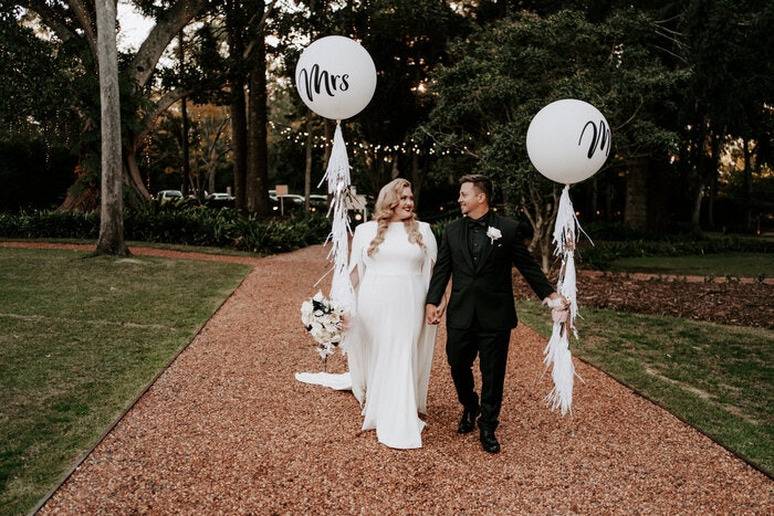 Bride and groom walking along the driveway holding balloons