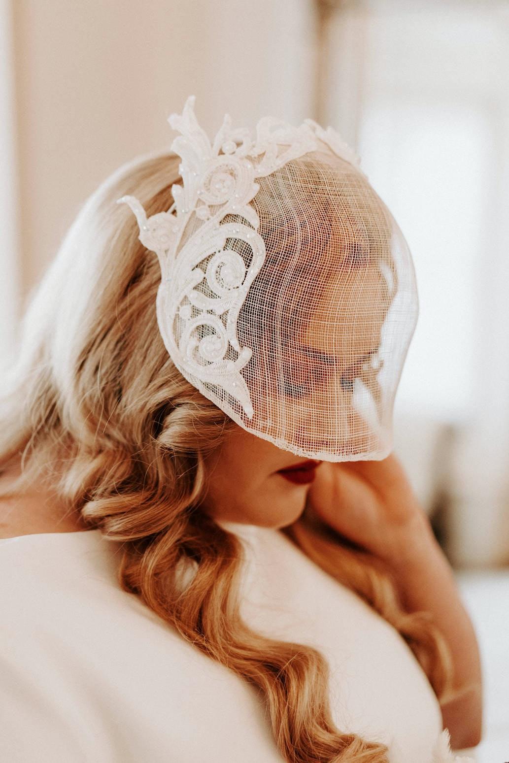 Bride wearing a short embellished veil covering half her face