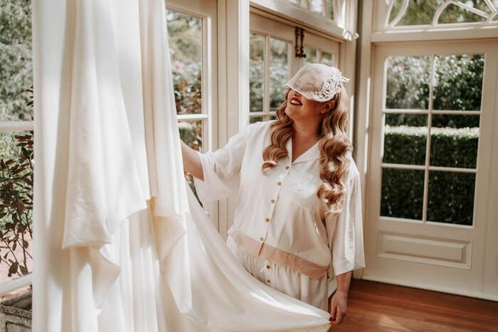 Bride gazing adoringly at her dress